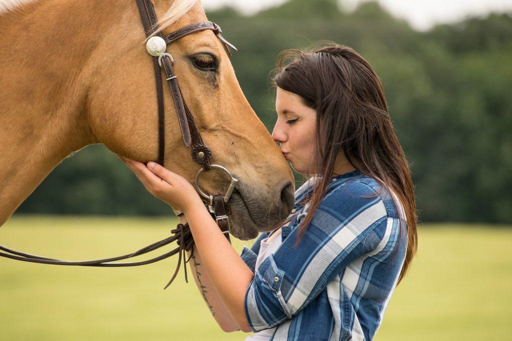 Femme qui embrasse un cheval sur le museau